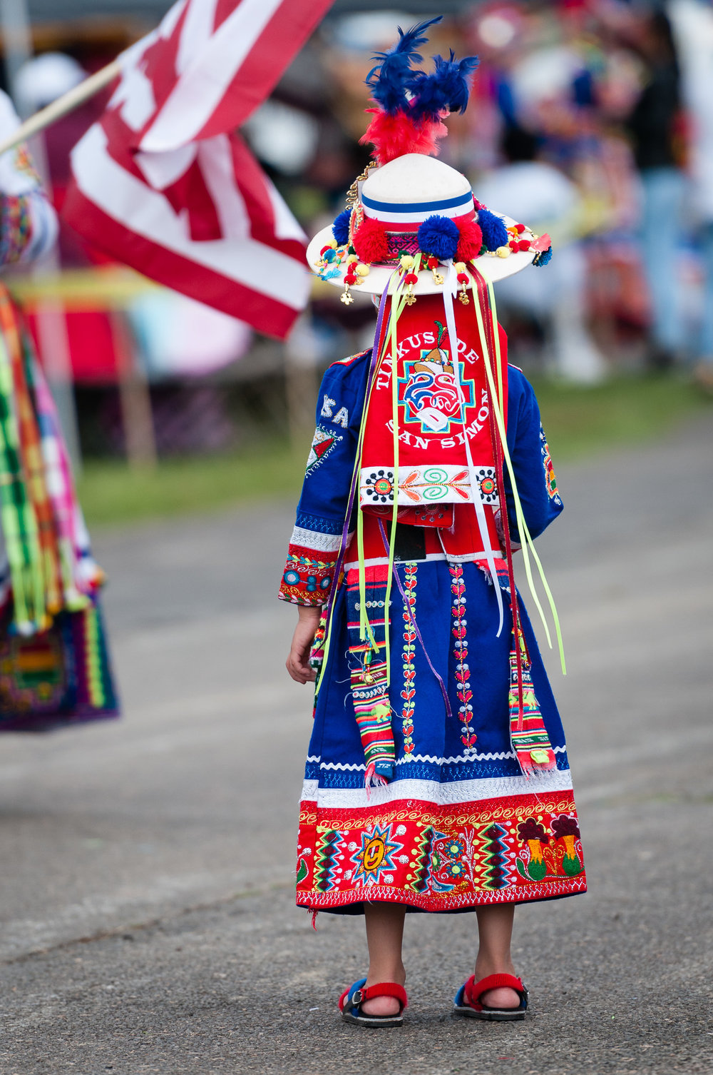 In this version I captured a lone young performer from Tinkus de San Simon USA, who had performed a Tinkus dance. She is facing away from me, looking towards the American flag and back towards the rest of her group. I really like the moments captured in these two images.