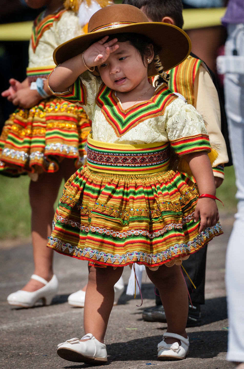 Here is a moment when a young performer from Salay Bolivia USA pauses, raising her hand to her head, just after her performance of a Salay dance.