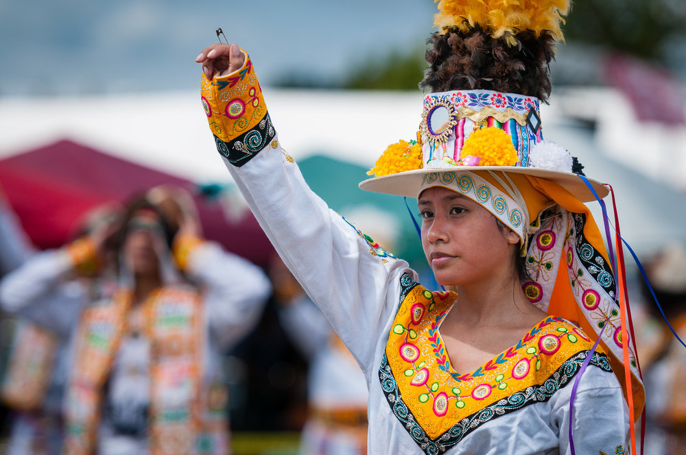 A performer with Fraternidad Alma Boliviana raises her hand at the end of, or just after, performing a Tinkus dance.