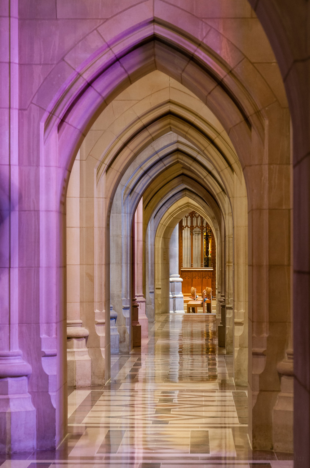 Colorful hallway illuminated by stained glass windows.