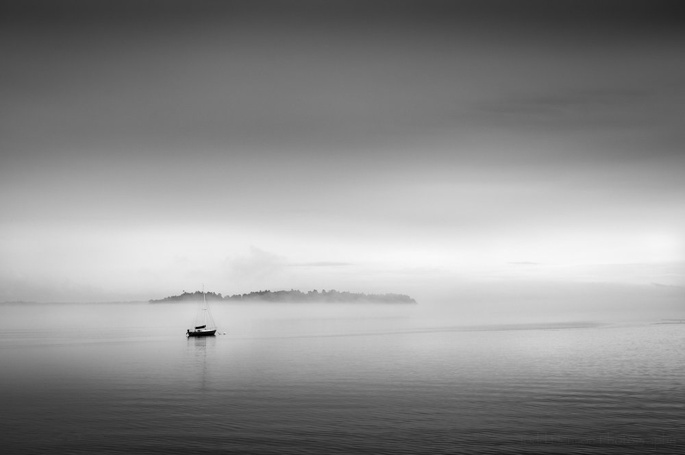 Black and white image of lone sailboat anchored before island in the fog on Casco Bay. Portland, Maine.