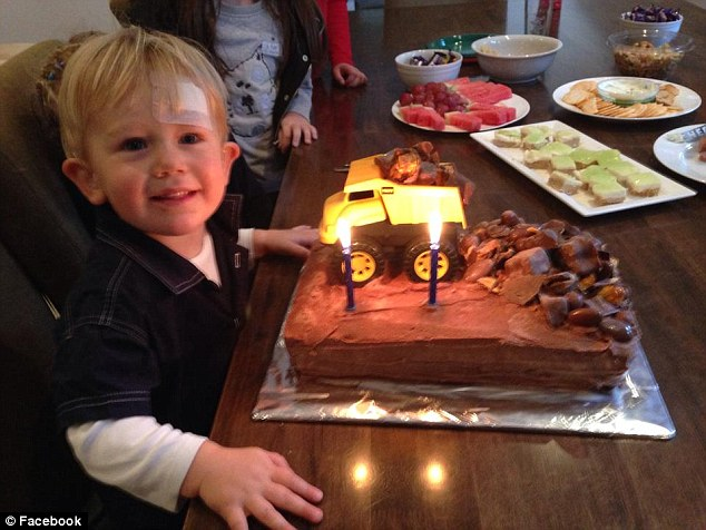 Lachlan celebrating his 2nd birthday in May, as his family delight in the fact that he can hear them sing 'Happy Birthday'