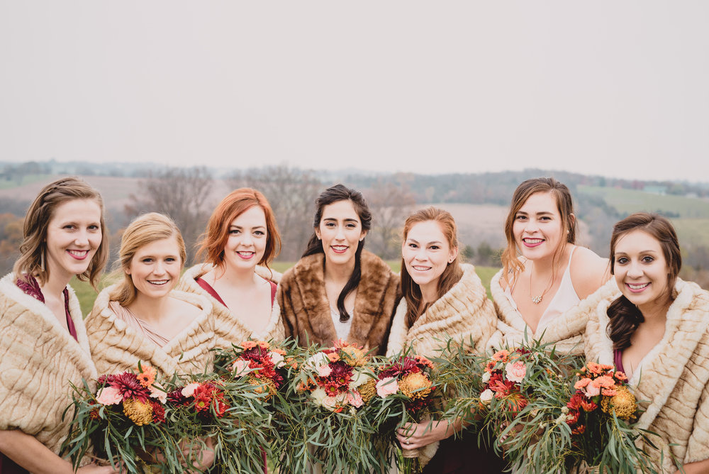 bride in vintage white and brown fur bridesmaids with fur and burgundy dresses outdoor bridal party photos .jpg