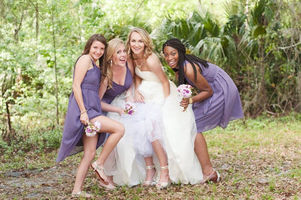 bride in white and platform shoes bridesmaids in purple outdoor florida wedding photos.jpg
