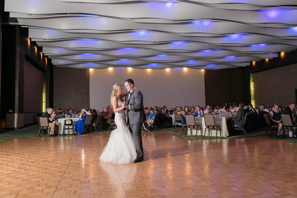 iowa-wedding-beaded-dress-cedar-rapids-planned-by-mostly-becky-weddings-reception-white-wedding-cake-blue-linen-purple-centerpieces-first-dance-ballroom-reception