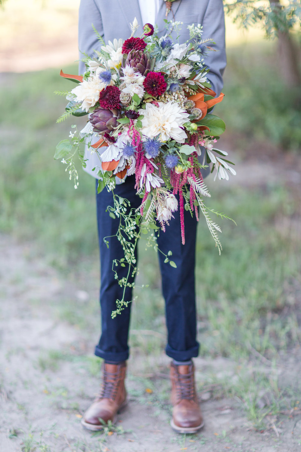 country-lane-lodge-adel-iowa-wedding-venue-iowa-wedding-planned-by-mostly-becky-weddings-boho-wedding-orange-purple-flowers-blue-suite-brown-boots-outdoor-ceremony-groom-bouquet