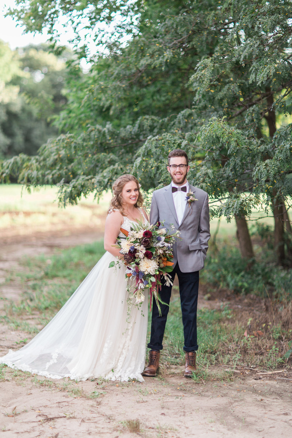 country-lane-lodge-adel-iowa-wedding-venue-iowa-wedding-planned-by-mostly-becky-weddings-boho-wedding-orange-purple-flowers-blue-suite-brown-boots-outdoor-ceremony