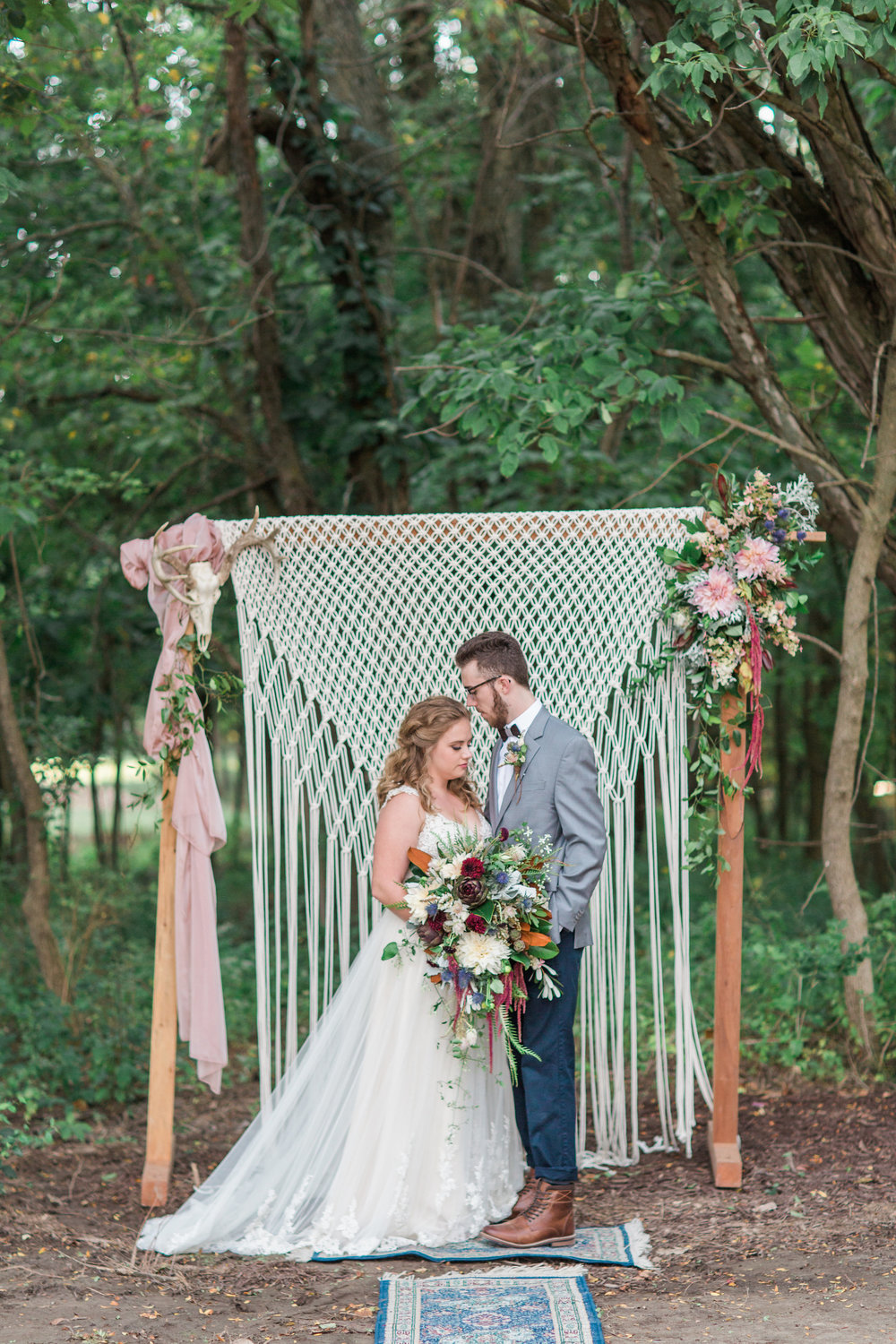 macrame-skull-country-lane-lodge-adel-iowa-wedding-venue-iowa-wedding-planned-by-mostly-becky-weddings-boho-wedding-orange-purple-flowers-blue-suite-brown-boots-outdoor-ceremony-