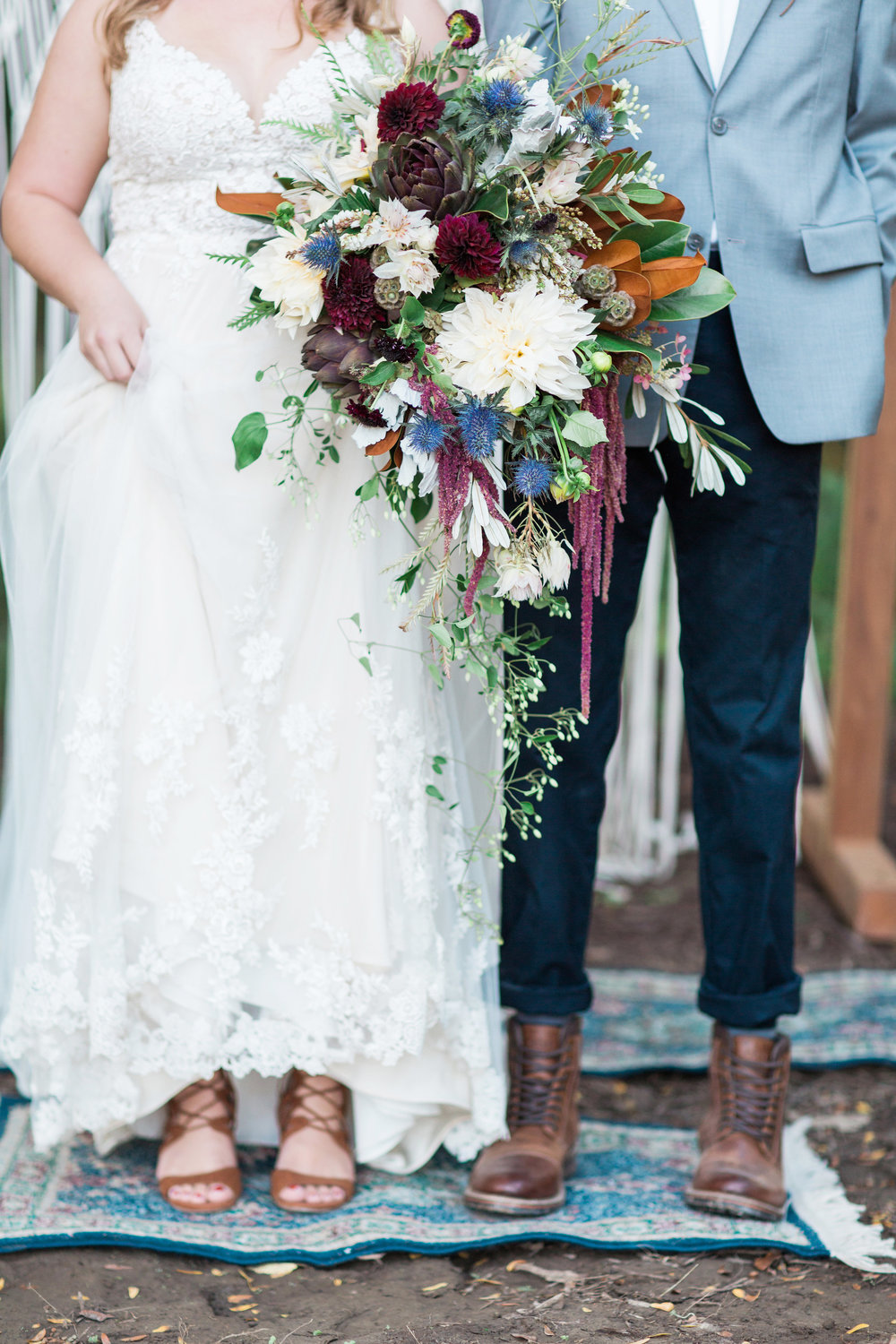 country-lane-lodge-adel-iowa-wedding-venue-iowa-wedding-planned-by-mostly-becky-weddings-boho-wedding-orange-purple-flowers-blue-suite-brown-boots-outdoor-ceremony-outdoor-rugs-macrame