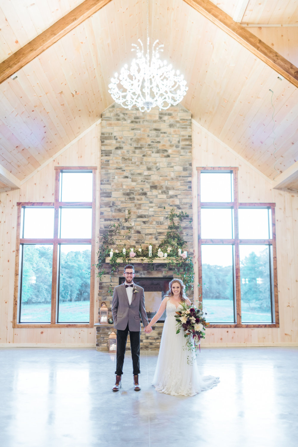 country-lane-lodge-adel-iowa-wedding-venue-white-lace-dress-purple-red-lush-bouquet-planned-by-mostly-becky-weddings-ceremony-lodge-wedding-chandelier