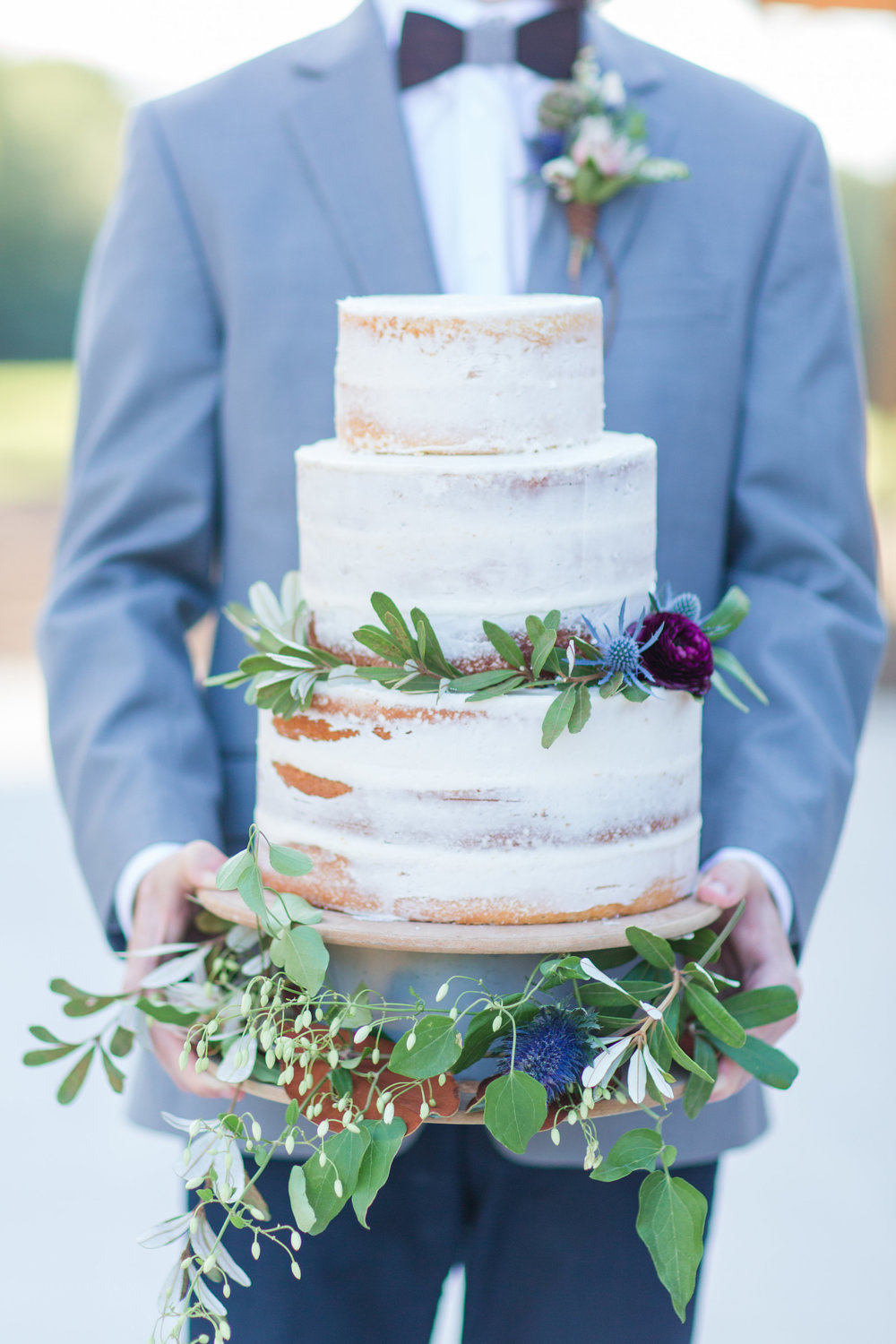country-lane-lodge-adel-iowa-wedding-venue-white-lace-dress-purple-red-lush-bouquet-planned-by-mostly-becky-weddings-ceremony-lodge-wedding-chandelier-cowhide-sweetheart-table-barn-table-lodge-wedding-groom-cake-bowtie-blue-suit-naked-cake