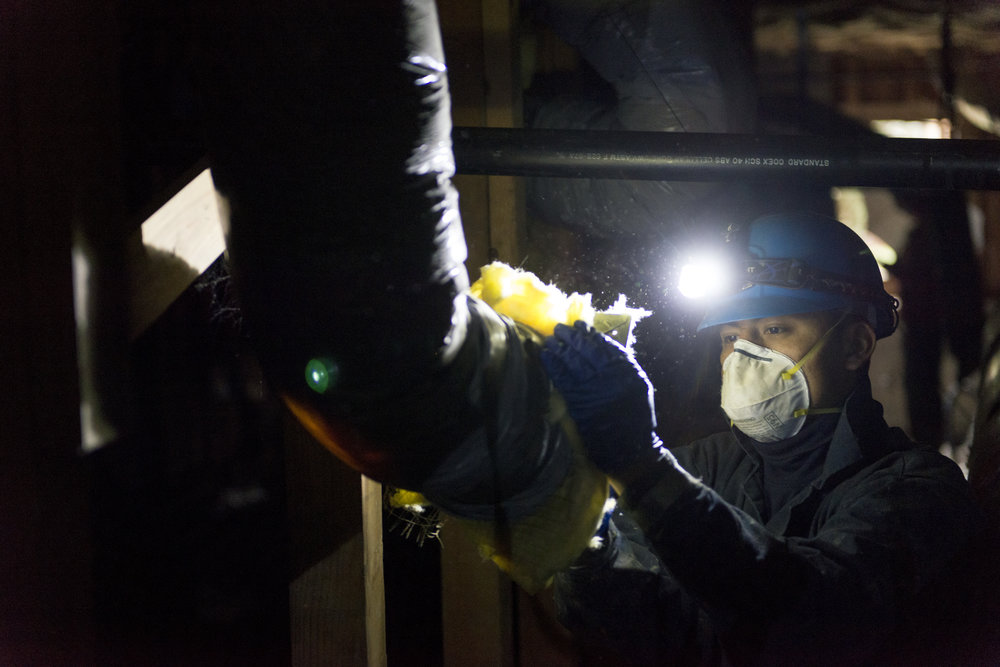 A contractor insulates a customers' air ducts.  Photo courtesy of and copyright Puget Sound Energy.
