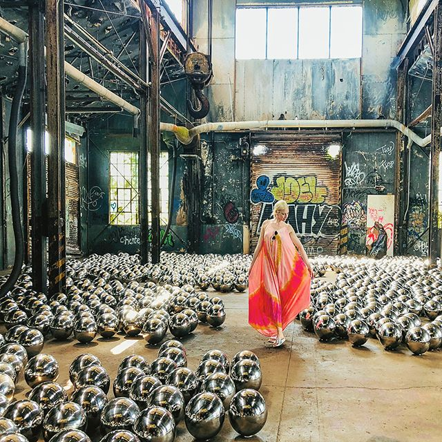 "✨ Peacock Plumes on for Kusama's Rockaway iteration of Narcissus Garden, comprised of 1,500 mirrored stainless steel spheres, it's on view in a former train garage that dates to the time when Fort Tilden was an active US military base 🔮 Narcissus Garden was first presented in 1966, when Kusama staged an unofficial installation and performance at the 33rd Venice Biennale. The silver spheres, originally made from plastic, were installed on the lawn in front of the Italian Pavilion, reflecting the landscape of the exhibition grounds. Kusama herself stood among them, 👣 barefoot and dressed in a gold kimono, alongside yard signs inscribed with the words ""Narcissus Garden, Kusama"" and ""Your Narcissism for Sale"" 🌿 Throughout the opening day of the exhibition, Kusama remained in the installation, tossing the spheres in the air and offering to sell them to visitors for 1,200 lire (approximately $2) each 💸 The action, which was viewed both as self-promotion and a critique on the commercialization of contemporary art, would later be seen as a pivotal moment in Kusama's career as she transitioned from installation toward the radical, politically charged public performances that would be the focus of her work in the late 1960s in NYC // @themuseumofmodernart"