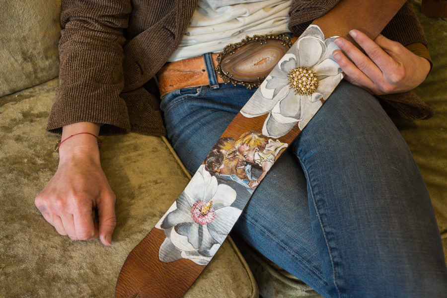 Linny's guitar strap with a painting of her and her grandfather, and flowers with antique pieces.