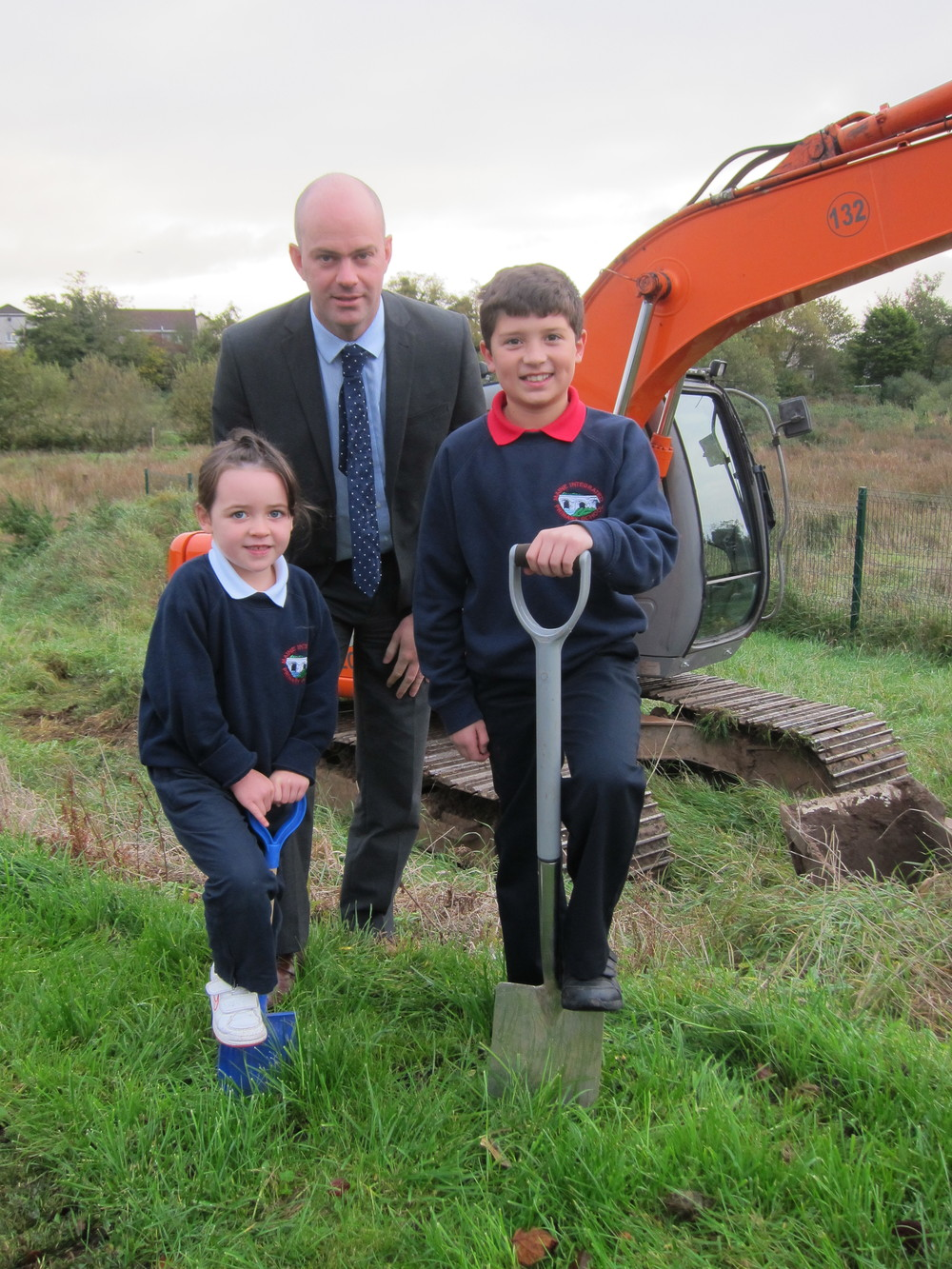 Grace McGarry (P2) and Mathew Topkul (P7) cutting ground on the new building works with Mr Costelloe