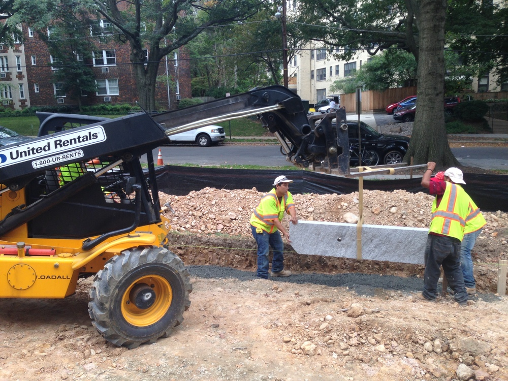 Setting a 600 lbs granite curb.