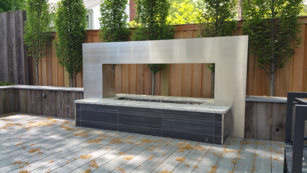 Close-up of custom stainless steel fire-pit with tile risers and granite cap.