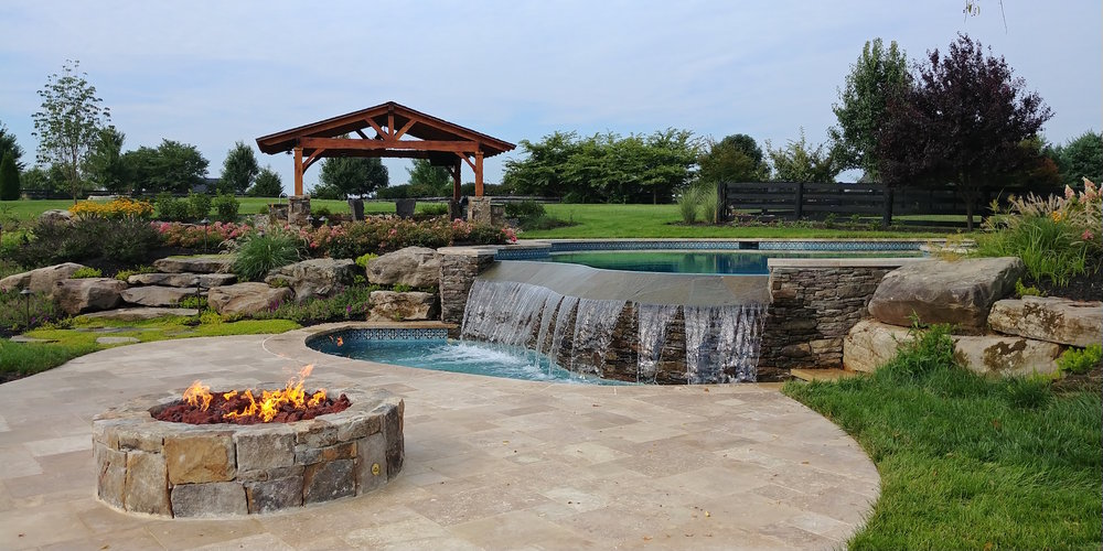 Our wonderful backyard sanctuary in Aldie Virginia that includes and infinity pool (with wading basin), fire pit and outdoor covered kitchen.