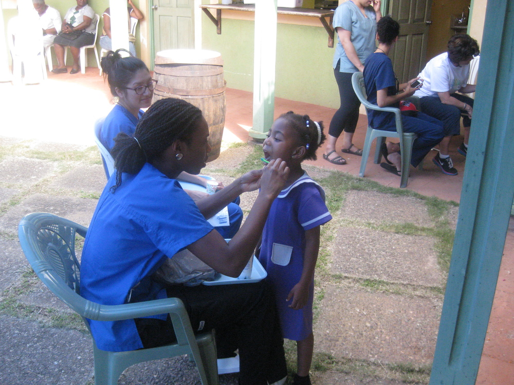 Hygienist students Rachel Power-Fardy and Tinika James giving fluoride treatment to the kids.