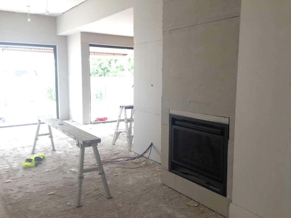 Plasterboard has gone up - and new fireplace installed in living room. You can just make out the black window frames across the kitchen and dining/living area.