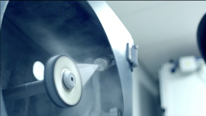 As lovely as they are, machined surfaces are not up to Apple's standards. In this segment of the video, two Kuka robotic arms with custom end actuators spin the Mac Pro's enclosure around polishing wheels to produce a near-mirror surface finish. Just as the enclosure is moved onto the internal polishing station, the machine spits a fresh load of polishing compound onto the wheel.