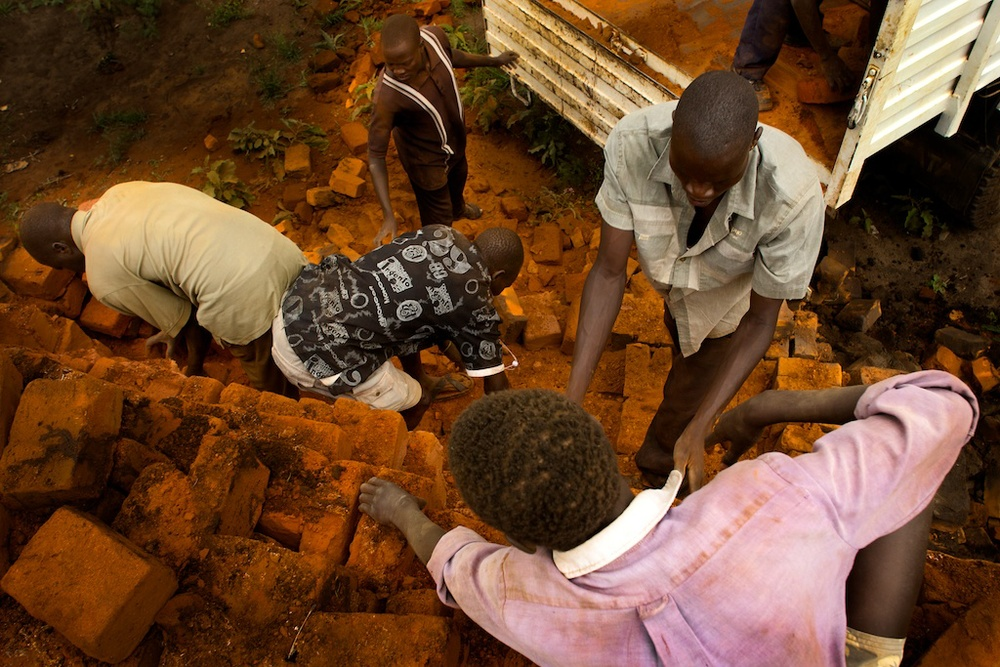 Karamoja workers transfer bricks onto a truck from a kiln pile near Kaabong, Uganda.