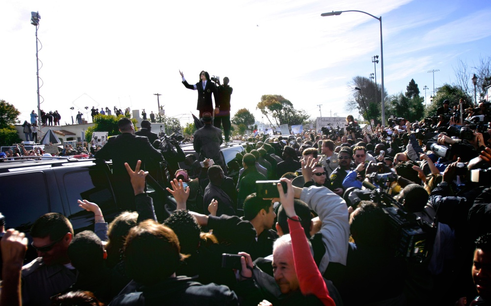 Standing before a cheering crowd atop his guarded transport, Michael Jackson greets fans and media after his arraignment in Santa Maria, Calif. Jackson pled innocent to all charges.