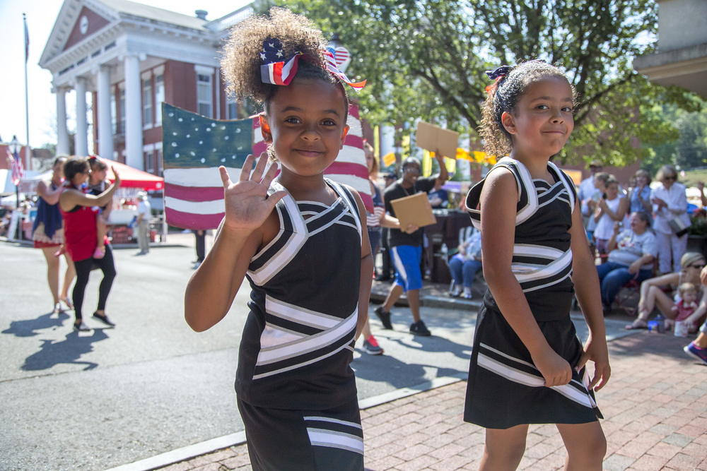 Two adorable girls walk in the parade, with an american flag mural behind them.