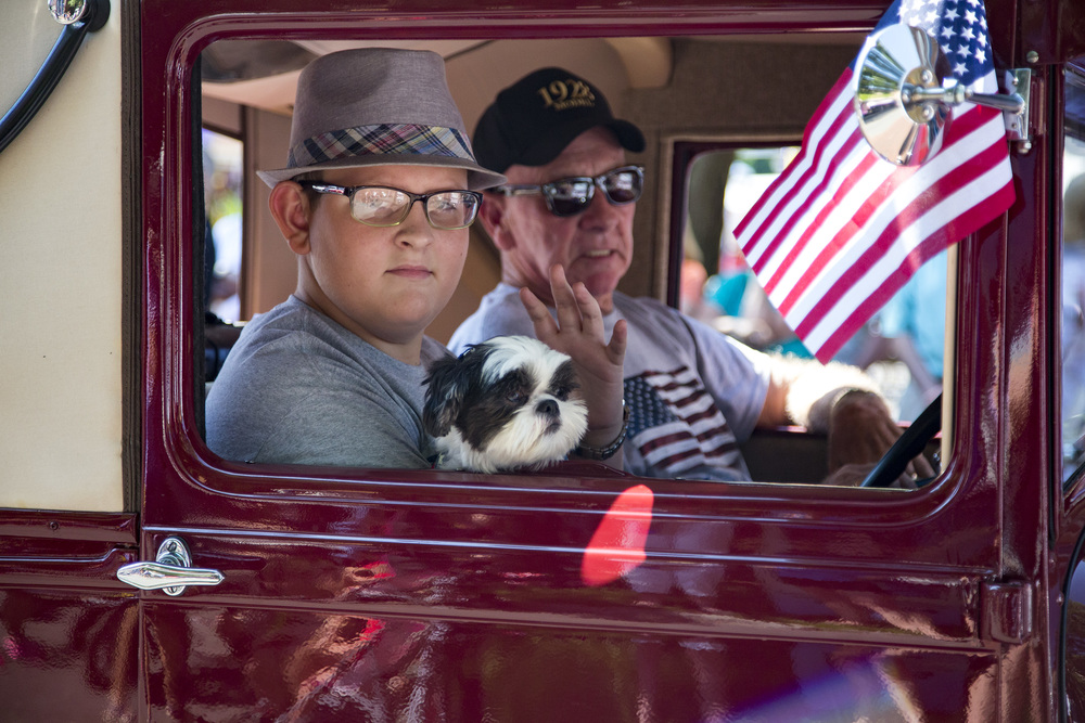 A man, a boy and a dog ride in a shiny antique vehicle, taking us back to another era.