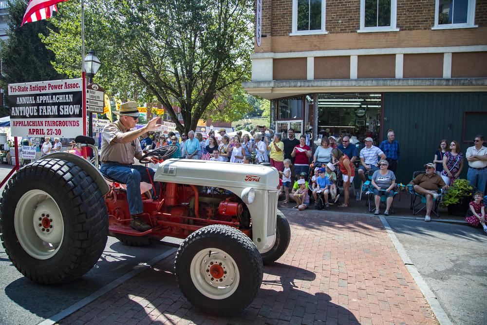 The crowd cheers and laughs as a man honks the horn of his tractor. Jonesborough, Tennessee.