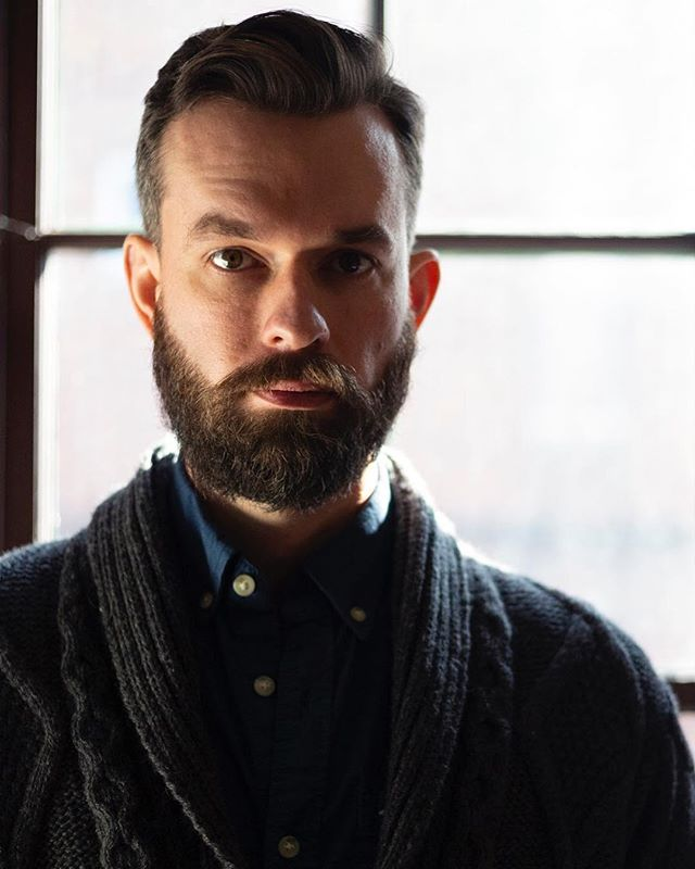 @benstaham poses in a smoking sweater; imaginary tobacco pipe out of frame.