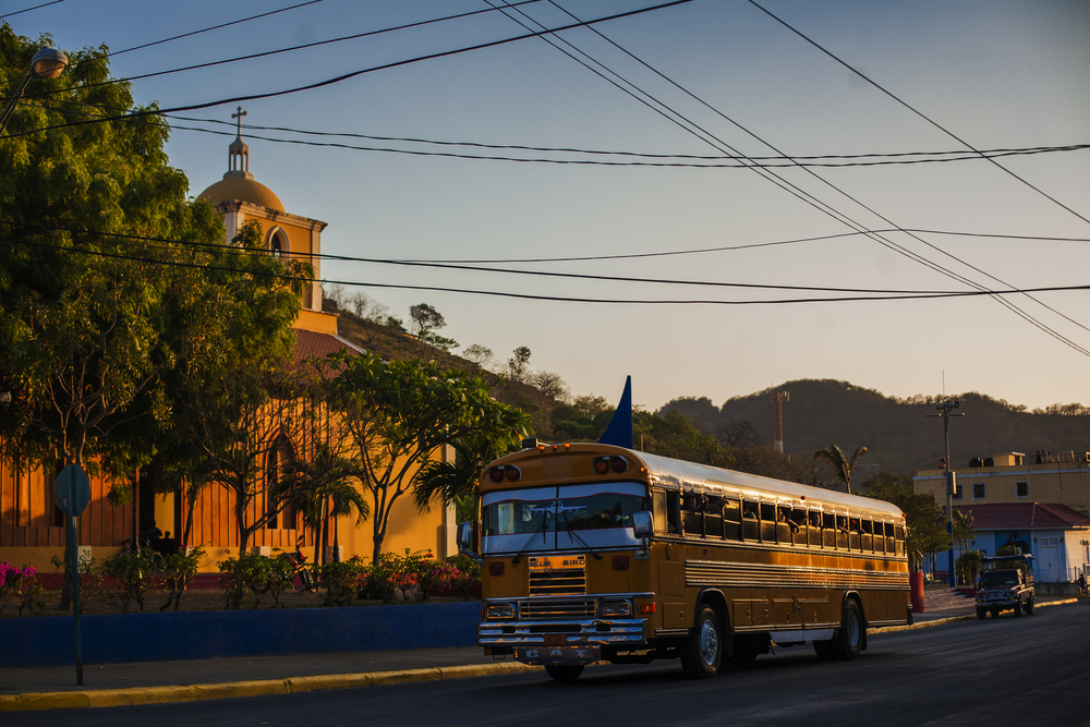 "Yellow ""Chicken bus"" in front of the church in San Juan"