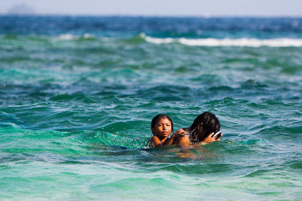 Kuna woman snorking with kid on her back. San Blas