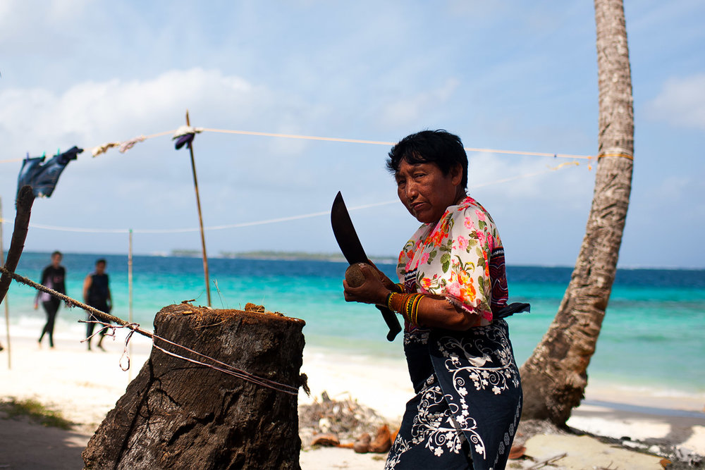 Kuna woman splitting a Coconut