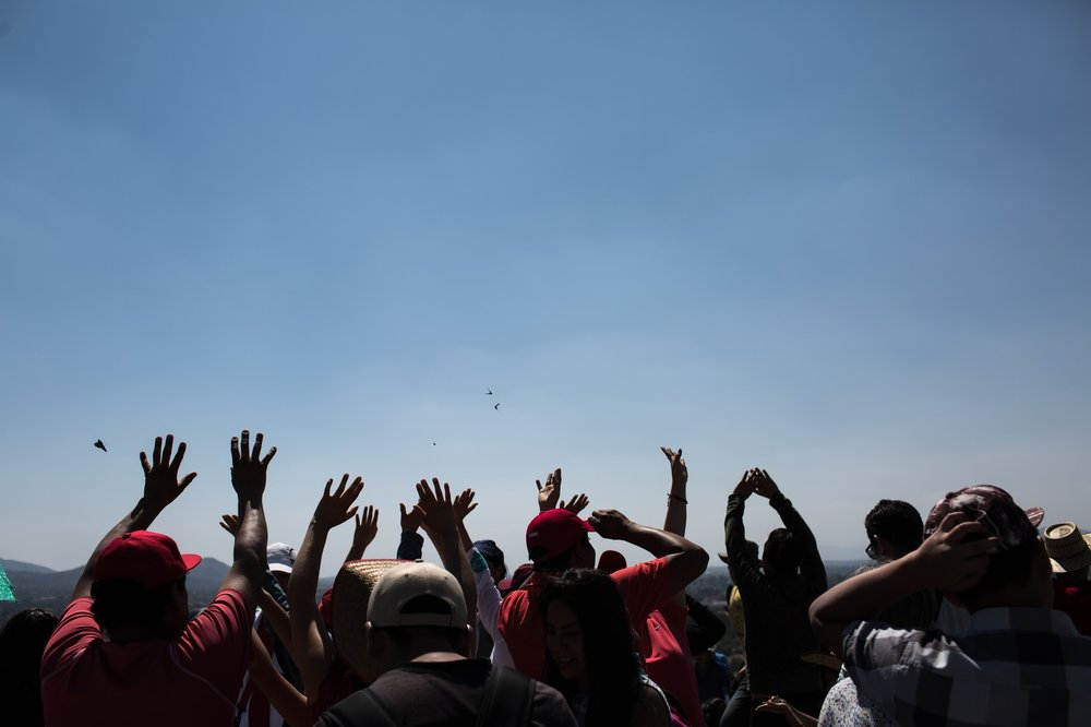 People raising hands towards the sun while standing on top of the  Pyramid of the Sun,   Teotihuacan ,