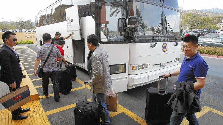 Chinese tourists board a bus with bags and suitcases of merchandise after shopping at the Desert Hills Premium Outlets in Cabazon in March 2013. (Allen J. Schaben / Los Angeles Times)