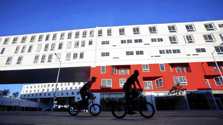 Photo Credit: Mel Melcon, Los Angeles Times.Bicyclists pass the new One Santa Fe apartment building in the downtown arts district.