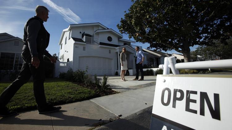 Prospective home buyers Theresa and Dustin Dobson wait for their real estate agent, Jim Crane, left, before checking out a home in Westchester in December. (Genaro Molina/Los Angeles Times)