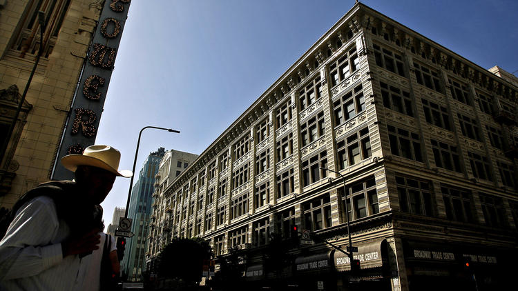 The Broadway Trade Center, at right, in downtown Los Angeles. The old department store will be converted to a combination shopping mall, office building and hotel, and will have two swimming pools, rooftop gardens and restaurants. (Katie Falkenberg / Los Angeles Times)