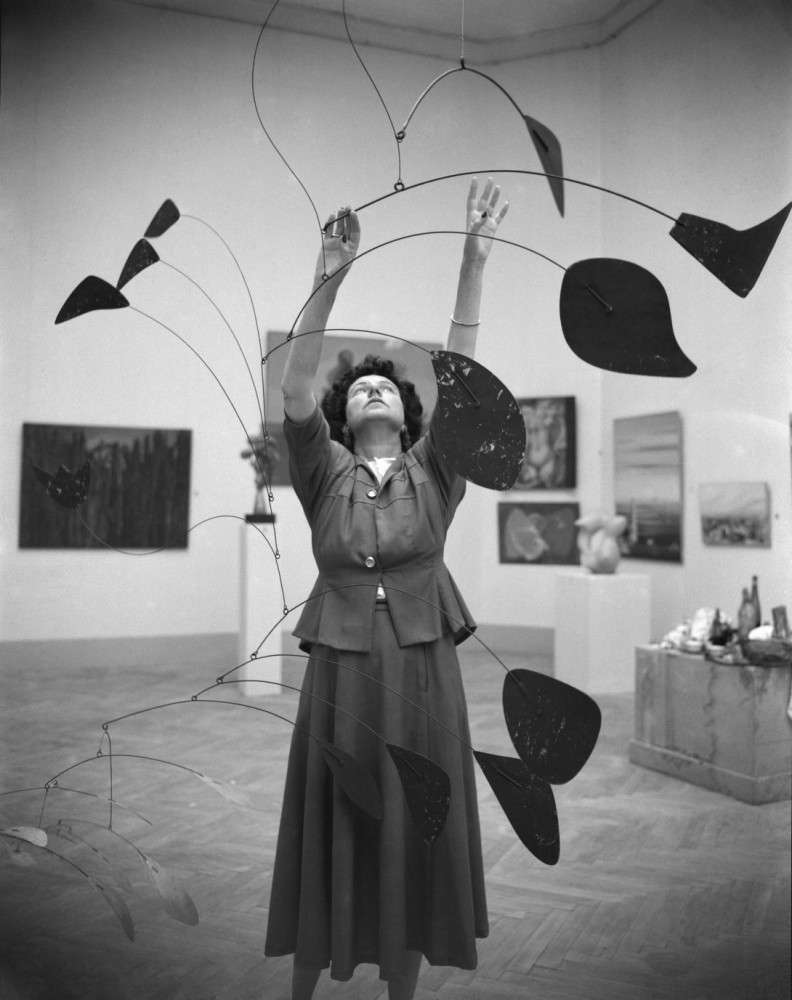 Peggy Guggenheim, renowned patron of the arts, hanging an Alexander Calder