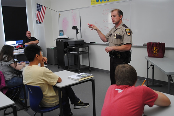 Minnesota State Patrol Sgt. Jesse Grabow talks about the dangers of distracted drivers during a guest presentation to students studying for their driver's license at WDC High School. At left, in back, pictured is WDC High School driver's education instructor Mike Ortmann.
