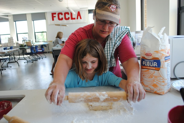 Lois Schulz shows Lily Adkins how to roll out her pie crust during the Bake and Take Camp, sponsored by WDCB Community Education.