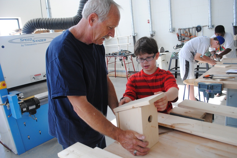 Sean Carlson places the top of his birdhouse while Mike Holzer holds it.
