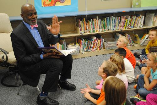 "Justice Alan Page shows WDC second-graders his ""perfectly pointy, impossibly perpendicular pinky"" Wednesday in the WDC Elementary media center."