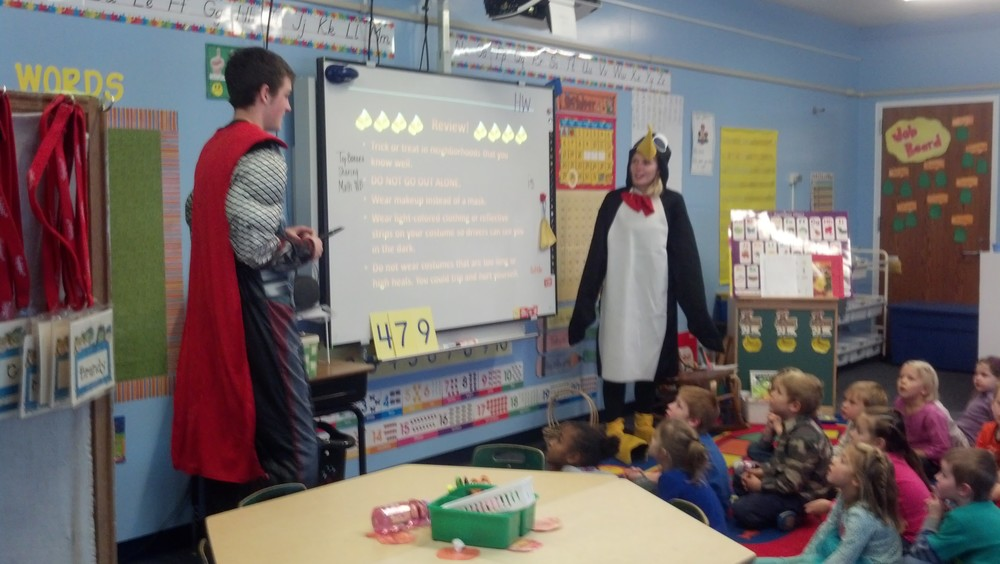 Dressed in their Halloween costumes, Wadena-Deer Creek BPA members Matthew Quincer, left, and Brandee Bly present Halloween safety tips to kindergartners on Oct. 28. (Photo by Jessica Langer, WDC Schools)