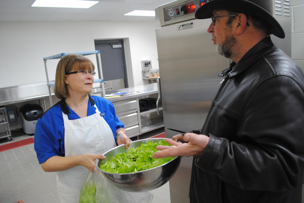 Lewis hands head cook Darla Hayes the first crop of lettuce.