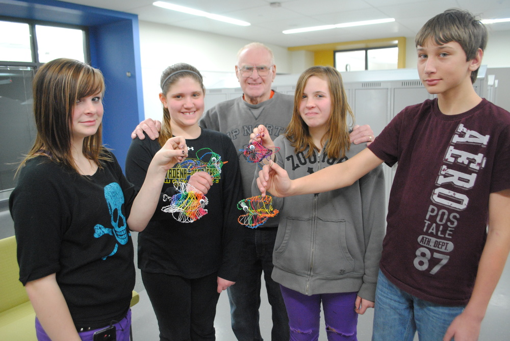 Wadena artist Chuck Richards, middle, is surrounded by some of the sixth-grade students who recently participated in his artist-in-residency. Students created colorful fish wire art. Pictured from left is Emmalee Toon, Laura Krause, Richards, Paige Welshan and Dylan Kern. (Photo by Dana Pavek, WDC Schools)