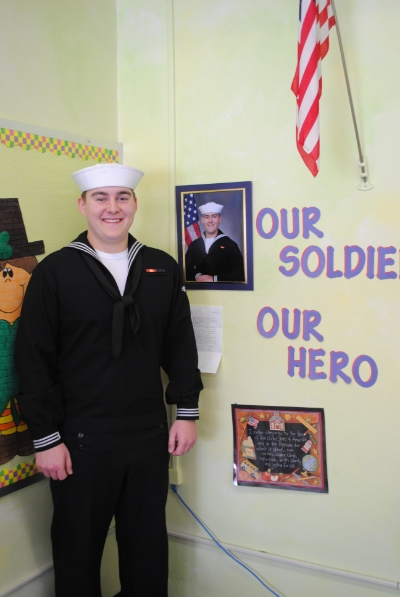 "Eliah Anderson stands next to display created by Mrs. Jackson in honor of their ""adopted solider."" Anderson said he was very touched by the display of respect and enthusiasm the WDC students and Mrs. Jackson expressed toward him."