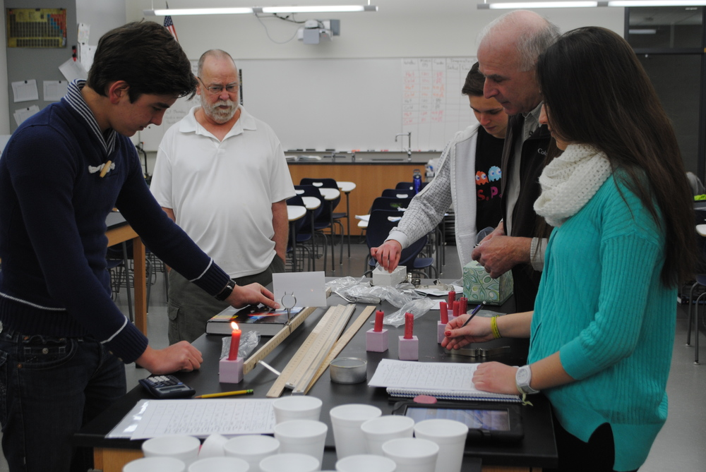 WDC students are conducing a physics exercise measuring focal lengths. Pictured from left: student Fernado Lopez, Craig Klawitter, Jim Nies and Maria Gonzalez. (Photo by Dana Pavek, WDC Schools)