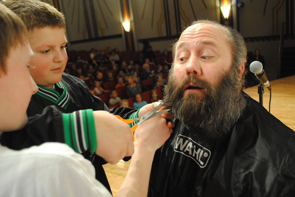 Dan Savoie is keeping a close eye on WDC students Payton Rondestvedt, left, and Josh Dykhoff, as they begin to cut off Savoie's beard for a cancer fundraiser Friday afternoon. (Photos by Dana Pavek, WDC Schools)